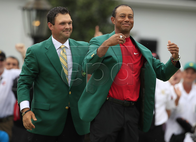 Patrick Reed of the US helps Tiger Woods of the US into his fifth green jacket after winning the 2019 Masters Tournament at the Augusta National Golf Club in Augusta, Georgia, USA, 14 April 2019. The 2019 Masters Tournament is held 11 April through 14 April 2019. EPA-EFE/TANNEN MAURY