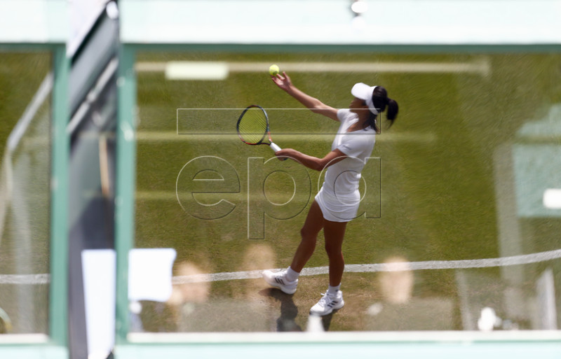 Su-Wei Hsieh of Taiwan (reflected in a window) in action against Kirsten Flipkens of Belgium during their second round match at the Wimbledon Championships at the All England Lawn Tennis Club, in London, Britain, 03 July 2019. EPA-EFE/NIC BOTHMA EDITORIAL USE ONLY/NO COMMERCIAL SALES