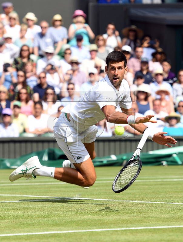 Novak Djokovic of Serbia takes a fall as he plays Roberto Bautista Agut of Spain in their semi final match during the Wimbledon Championships at the All England Lawn Tennis Club, in London, Britain, 12 July 2019. EPA-EFE/ANDY RAIN EDITORIAL USE ONLY/NO COMMERCIAL SALES